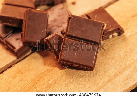 pieces of dark chocolate on a wooden background. #438479674