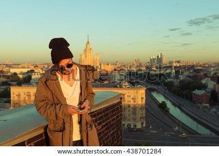 MOSCOW, RUSSIA - JUNE 13, 2016: Young and brave male sitting on the edge of high roof looking at phone similar to iphone and stunning view of city in the summer during dawn #438701284