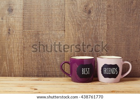 Coffee cups on wooden table with chalkboard sign and best friends text. Friendship day celebration background