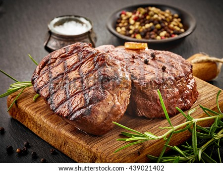 grilled beef steaks with spices on wooden cutting board Royalty-Free Stock Photo #439021402