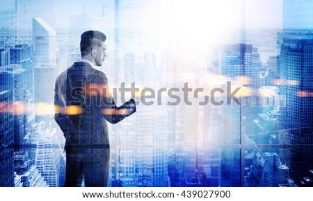 Stylish young businessman using smart phone on New York city background. Double exposure #439027900