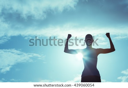 Girl power! Strong and confident woman flexing her muscle.  Royalty-Free Stock Photo #439060054