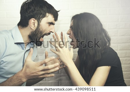 attractive angry couple fighting and shouting at each other Royalty-Free Stock Photo #439098511