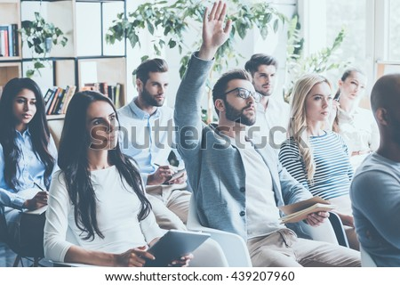 He got some questions. Group of young people sitting on conference together while one man raising his hand  Royalty-Free Stock Photo #439207960