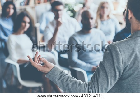 Business coach. Rear view of man gesturing with hand while standing against defocused group of people sitting at the chairs in front of him  Royalty-Free Stock Photo #439214011