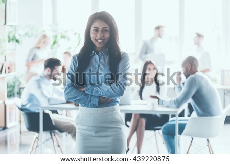 Feeling confident in her team. Beautiful young African woman keeping arms crossed and looking at camera with smile while her colleagues working in the background   #439220875