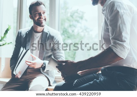 Sharing good news. Cropped image of two young businessmen in smart casual wear talking and smiling while sitting on the window sill in office  #439220959