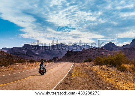 Biker driving on the Highway on legendary Route 66 to Oatman, Arizona. Royalty-Free Stock Photo #439288273