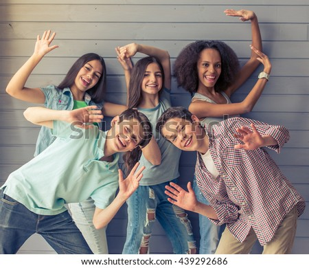 Group of teenage boys and girls is looking at camera, showing palms and smiling while standing against gray wall #439292686