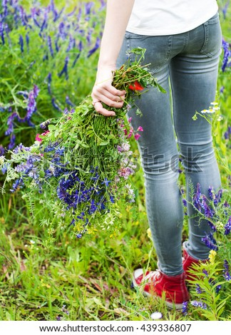 girl holding a bouquet of wildflowers - arms and legs close-up #439336807