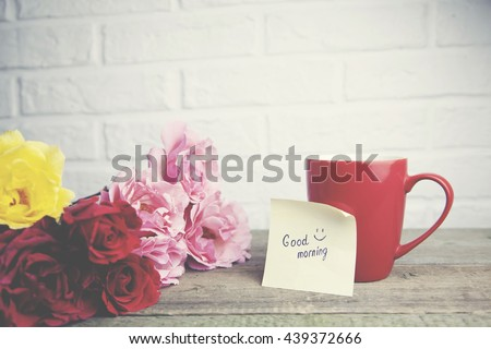 Coffee cup with rses and notes good morning on wooden table on brick wall background