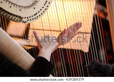 Hands of the woman playing a harp. Symphonic orchestra. Harpist close up. Royalty-Free Stock Photo #439389379