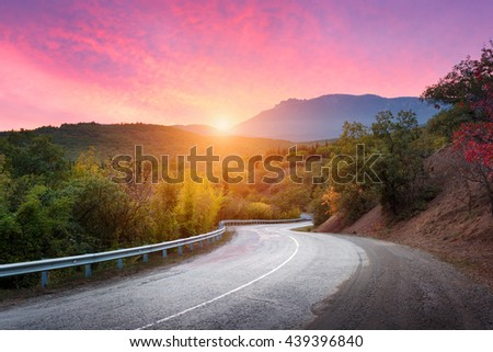 Mountain road passing through the forest with dramatic colorful sky and red clouds at colorful sunset in summer. Mountain landscape with road. travel background #439396840