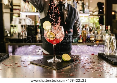 Expert barman is making cocktail at night club. Royalty-Free Stock Photo #439422121