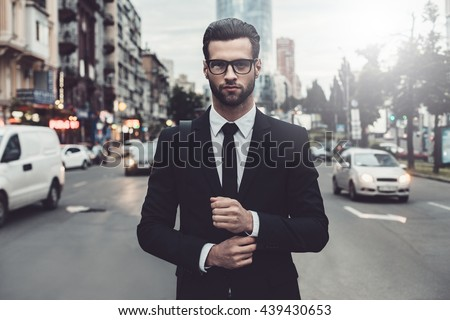 Confident businessman. Confident young man in full suit adjusting his sleeve and looking away while standing outdoors with cityscape in the background Royalty-Free Stock Photo #439430653