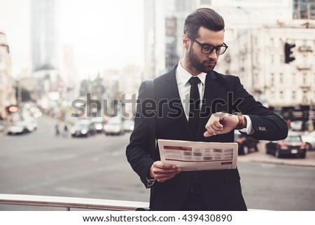 I should be there in time. Confident young man in full suit holding newspaper and looking at his watch while standing outdoors with cityscape in the background Royalty-Free Stock Photo #439430890