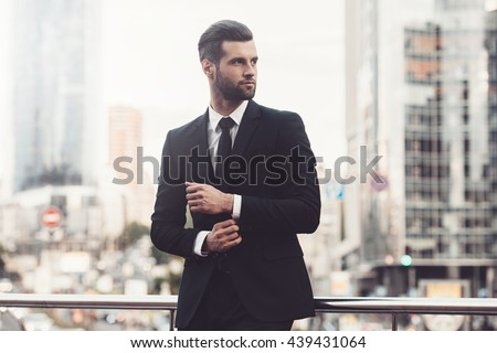 Modern businessman. Confident young man in full suit adjusting his sleeve and looking away while standing outdoors with cityscape in the background Royalty-Free Stock Photo #439431064