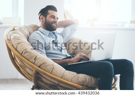 Surfing web at home. Handsome young man working on laptop and smiling while sitting in big comfortable chair at home   #439432036