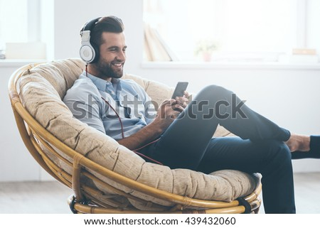 Listening to his favorite music. Handsome young man in headphones looking at his smart phone and smiling while sitting in big comfortable chair at home   #439432060