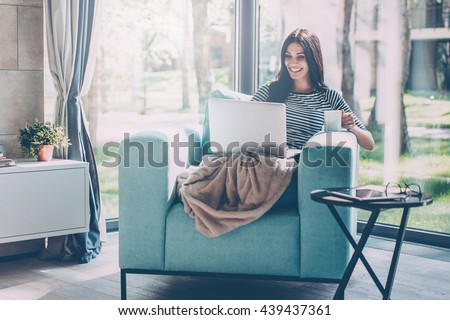 Enjoying time at home. Beautiful young smiling woman working on laptop and drinking coffee while sitting in a big comfortable chair at home  #439437361