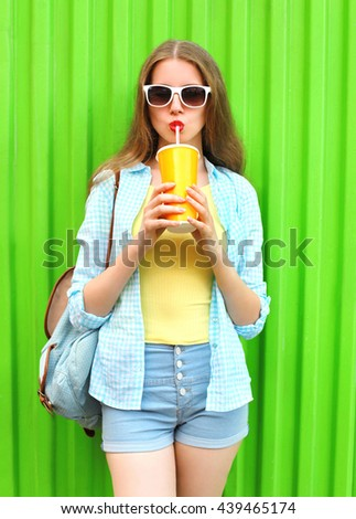 Pretty woman in sunglasses drinking fruit juice from cup over colorful green background #439465174