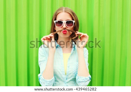 Woman having fun shows moustache hair over green background #439465282