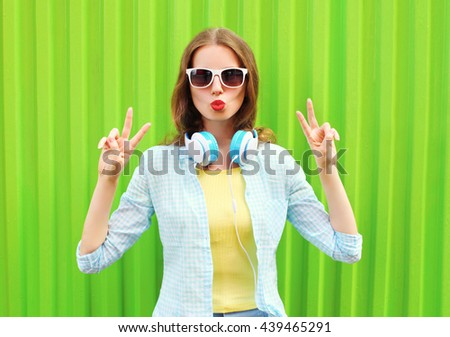 Pretty cool woman listens to music in headphones over green background #439465291