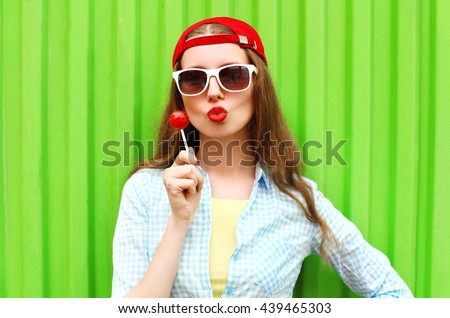 Fashion portrait pretty cool girl with lollipop over green background #439465303