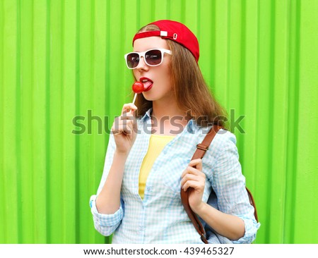 Portrait pretty cool girl with lollipop over green background #439465327