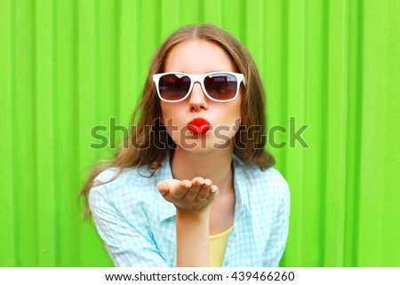 Woman in white sunglasses sends an air kiss over colorful green background #439466260