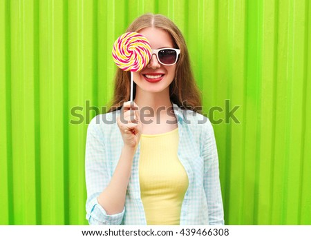 Portrait happy pretty smiling woman and lollipop over colorful green background #439466308