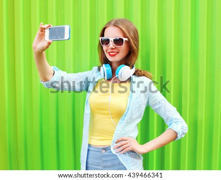 Pretty cool girl makes self portrait on smartphone over green background #439466341