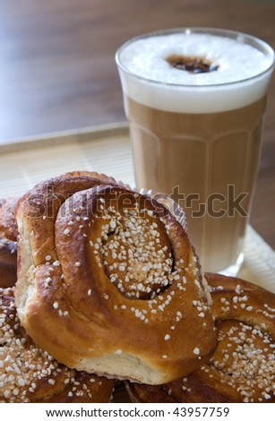 a glass of cappuccino and cinnamon buns #43957759