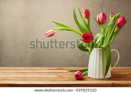 Tulip flowers for birthday celebration. Tulips in vase on wooden table #439829320