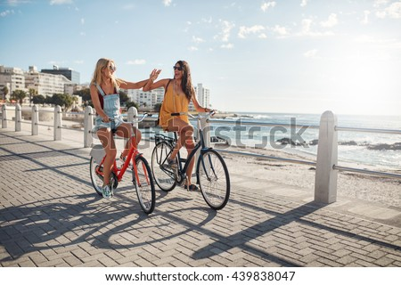 Two female friends riding cycles on the seaside promenade. Excited young women enjoying riding bicycles at the waterfront on a summer day. #439838047
