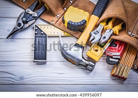Leather tool belt with construction tooling on wooden board maintenance concept. Royalty-Free Stock Photo #439956097
