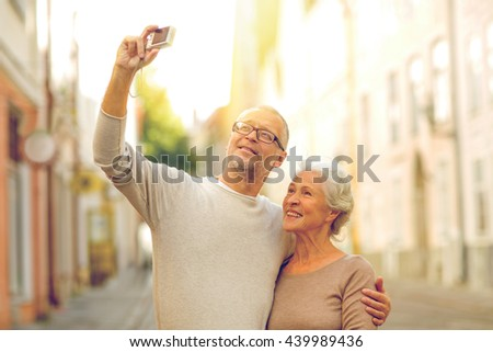 age, tourism, travel, technology and people concept - senior couple with camera taking selfie on street #439989436