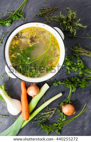 A large pot of homemade coocked fresh organic vegetable stock or broth with fennel, parsley, thyme, onions, carrot, mushrooms and leeks. Stone grey background with vegetables on it.