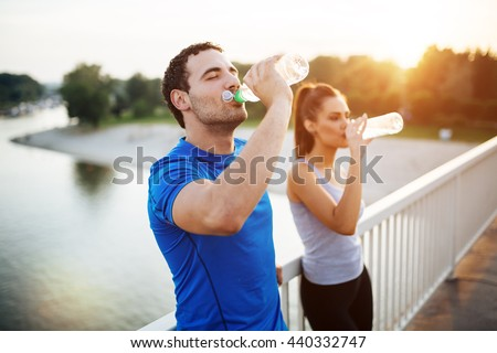 Couple staying hydrated after workout Royalty-Free Stock Photo #440332747