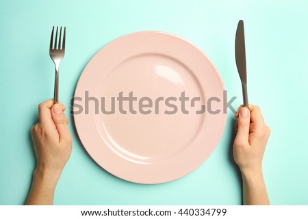 Female hands with cutlery and empty plate on turquoise background #440334799