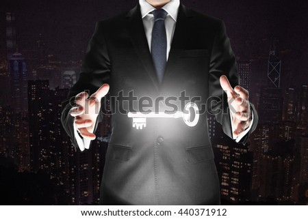 Businessman holding levitating key on abstract dark city background  #440371912