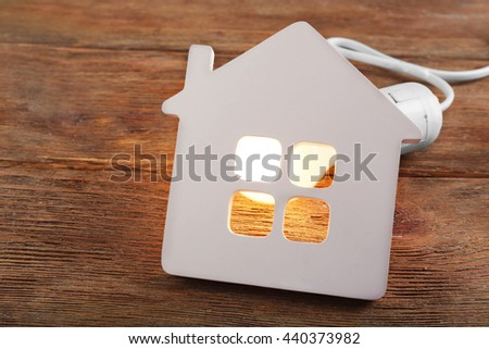 Bulb and shape of home on wooden background #440373982