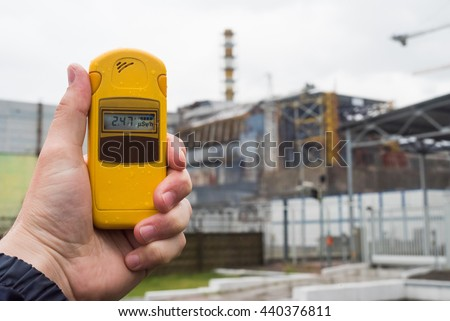 radiometer in hand with fourth Chernobyl reactor on the background #440376811