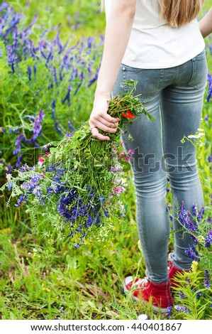girl holding a bouquet of wildflowers - arms and legs close-up #440401867