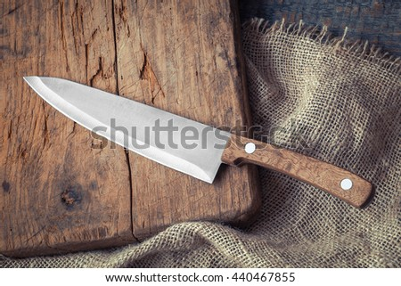 Big kitchen knife lying on an old cutting board #440467855