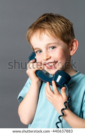 happy young red hair child with freckles talking on a blue old fashioned telephone for communication concept, grey background studio