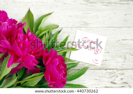 "Good morning! Bouquet of pink peonies and the white card with the inscription ""Good morning!"" on the old painted wooden background, copy space"