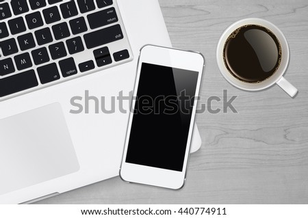 Smartphone on laptop keyboard and cofee cup with copy space on white or gray wood table #440774911