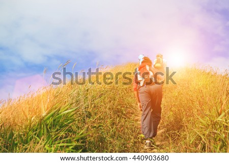 Hiker with backpack walking through a meadow on mountain, soft light and vintage color filtered. soft light and vintage color filtered. Travel and adventure concept. Success concept. Outdoor concept. #440903680