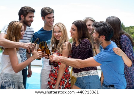 Group of friends toasting beer bottles while enjoying near pool #440913361